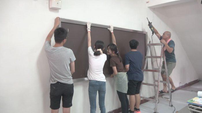 起手動腳,大夥將布告欄從牆上取下以便油漆。從暑假開始,一步一步改造東海社區!